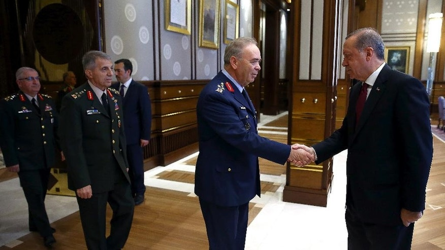Turkey President Recep Tayyip Erdogan, right, shakes hands with the Commander of Turkish Air Forces General Abidin Una during a meeting with the top-level military chiefs at the Presidential palace in Ankara, Turkey, on Friday, July 29, 2016. Erdogan met with Hulusi Akar, the four-star general who retained his position as chief of staff following a Supreme Military Council meeting, as well as other top military brass of the Turkish armed forces (Kayhan Ozer/Presidential Press Service, Pool Photo via AP)