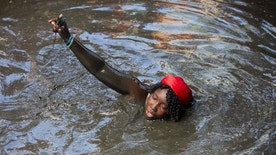 In this July 24, 2016 photo, a pilgrim takes a bath in a sacred mud pool during the annual Voodoo celebration in Plaine-du-Nord, Haiti, Saturday, July 23, 2016. Pilgrims come to bathe in the mud and make offerings expecting a miracle.  The village in northern Haiti is transformed over two days each July into the spiritual center of the Voodoo religion. (AP Photo/Dieu Nalio Chery)