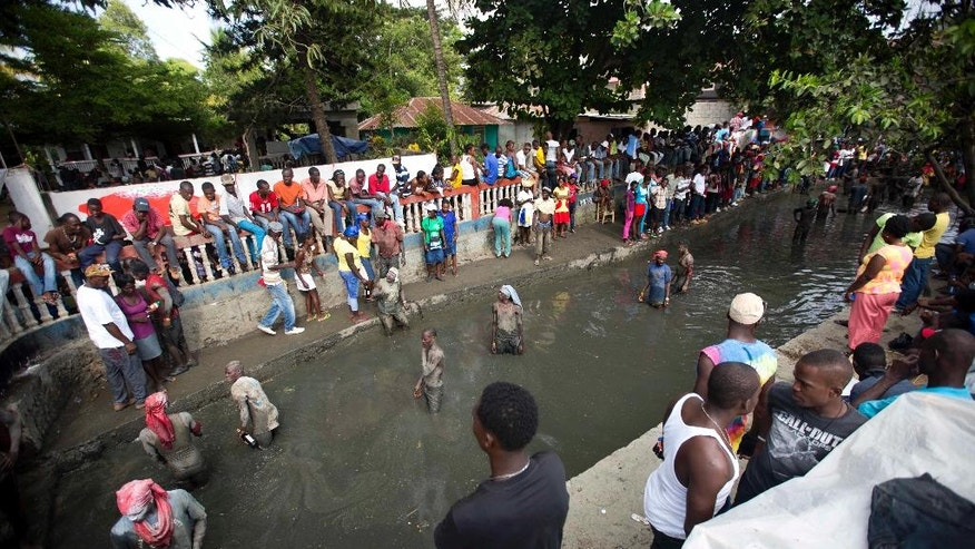 In this July 24, 2016 photo, pilgrims wade in a sacred mud pool as they attend a Voodoo ceremony in Plaine-du-Nord, Haiti. The village in northern Haiti is transformed over two days each July into the spiritual center of the Voodoo religion. Pilgrims bring flowers, rum, candles, meat, and throw them into the mud as offerings. (AP Photo/Dieu Nalio Chery)