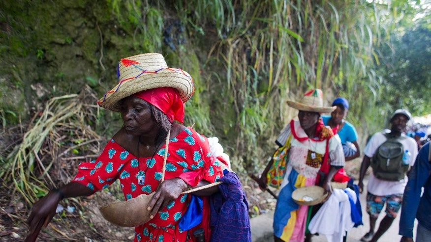 In this July 16, 2016 photo, Voodoo pilgrim Dieudone Beauvil, left, and her cousin Jesula Francois, following directly behind, walk from Mirebalais to Saut d' Eau, Haiti, to bathe in a waterfall believed to have purifying powers. After bathing in the waterfall they will throw away the garments they were wearing and put on new ones for good luck. (AP Photo/Dieu Nalio Chery)