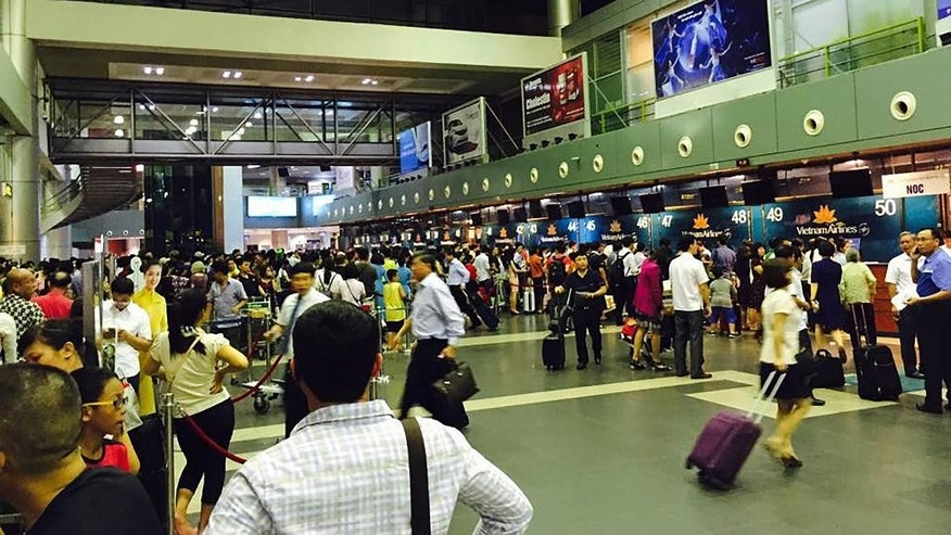 Passengers crowd at check-in counters at Noi Bai Airport in Hanoi, Vietnam Friday, July 29, 2016. Screens displaying flight information at Vietnam's two major airports, Noi Bai and Tan Son Nhat in Ho Chi Minh City, were hacked Friday to contain distorted information about the South China Sea and insult Vietnam and the Philippines, state media reported. (AP Photo)