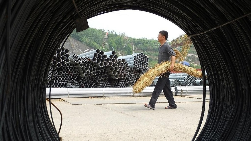 "In this Friday, April 29, 2016 photo, a man walks in a steel market in Yichang in central China's Hubei province. Beijing has criticized new European tariffs announced Friday, July 29, 2016 on Chinese steel as ""unjustifiable"" protectionism coming just weeks after commerce ministers from G20 nations pledged to promote free trade. (Chinatopix Via AP)"