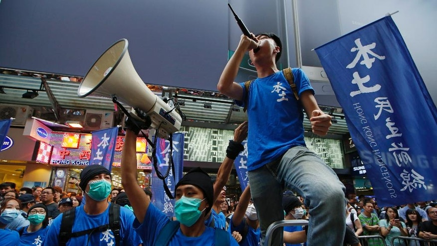 In this Saturday, July 11, 2015 photo, high-profile localist candidate, Edward Leung of Hong Kong Indigenous, right, shouts slogan during a demonstration in Hong Kong. As the Asian financial center prepares for legislative elections in September, a new wave of radical political activists are planning to join the campaign, including some who advocate the once-unthinkable idea of independence from China. (AP Photo/Kin Cheung)