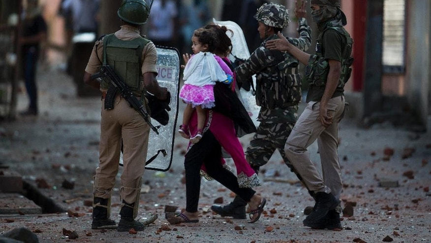 An Indian paramilitary soldier, second right, gestures to stone throwing protestors to stop as a Kashmiri woman carrying a child crosses the street during clashes between Kashmiri protestors and India troops in Srinagar, Indian controlled Kashmir, Thursday, July 28, 2016. Authorities lifted a curfew in most of parts of Indian-controlled Kashmir but shops and businesses remained shut due to a strike called to protest Indian rule in the Himalayan region. Kashmir's largest anti-India street protests in recent years were sparked by the killing of top rebel commander Burhan Wani by government forces July 8.(AP Photo/Dar Yasin)