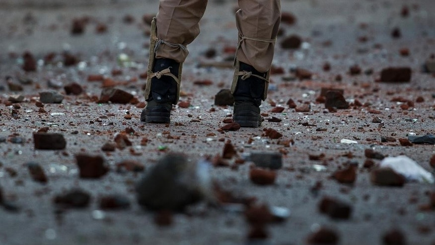 An Indian paramilitary soldier stands guard on a road dotted with stones, bricks and glass thrown at them by Kashmiri protesters during clashes in Srinagar, Indian controlled Kashmir, Thursday, July 28, 2016. Kashmir's largest anti-India street protests in recent years were sparked by the killing of top rebel commander Burhan Wani by government forces July 8. (AP Photo/Dar Yasin)