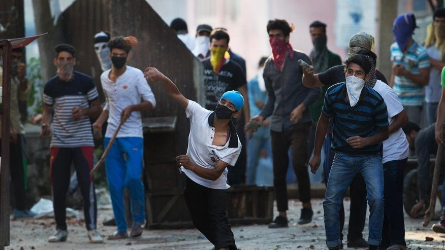 Masked Kashmiri protesters throw bricks at Indian paramilitary soldiers during a protest in Srinagar, Indian controlled Kashmir, Thursday, July 28, 2016. Authorities lifted a curfew in most of parts of Indian-controlled Kashmir but shops and businesses remained shut due to a strike called to protest Indian rule in the Himalayan region. Kashmir's largest anti-India street protests in recent years were sparked by the killing of top rebel commander Burhan Wani by government forces July 8. (AP Photo/Dar Yasin)