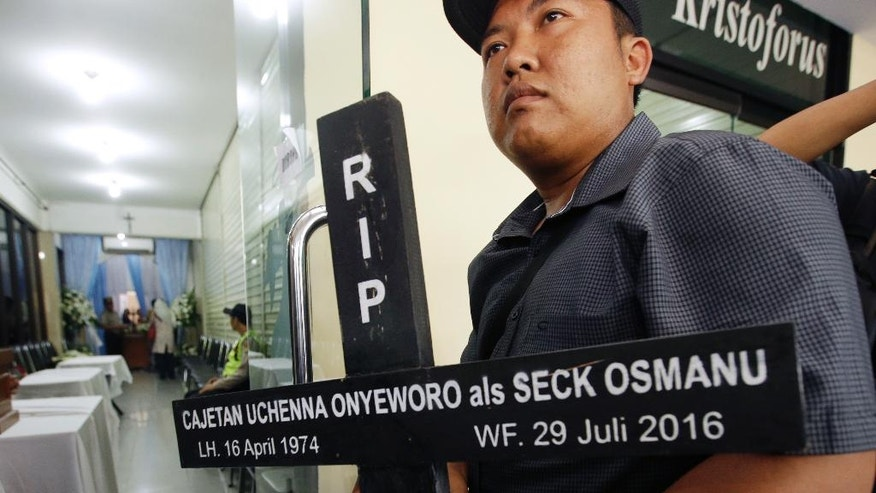 A worker hold a cross with name of death row prisoner Nigerians Seck Osmanu written on it at a funeral home in Jakarta, Indonesia, Friday, July 29, 2016. Indonesia executed four people convicted of drug crimes on Friday despite international protests and said it would decide later when as many as 10 others are put to death. (AP Photo/Achmad Ibrahim)