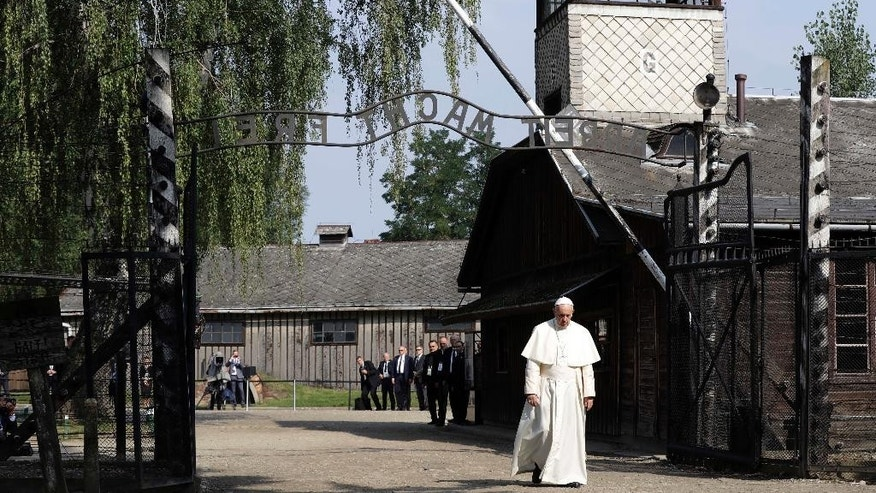 "Pope Francis walks through the gate of the former Nazi German death camp of Auschwitz in Oswiecim, Poland, Friday, July 29, 2016.  Pope Francis has walked beneath the notorious ""Arbeit Macht Frei"" gate at Auschwitz, beginning a somber visit to the Nazi German death camp. (AP Photo/Gregorio Borgia)"