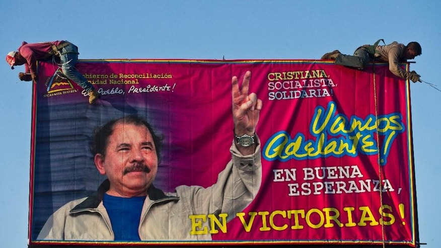 "FILE - In this Dec. 21, 2015 file photo, workers install a billboard supporting Nicaragua's President Daniel Ortega along a street Managua, Nicaragua. The banner's message reads in Spanish: ""Let's move ahead! In good hope, in victories!""  The Supreme Electoral Council unseated 16 opposition legislators from the Liberal Independent Party and its ally the Sandinista Renovation Movement Friday, July 29, 2016, for not recognizing their leader. That leader, Pedro Reyes, had recently been given that authority by the Supreme Court, which removed the party's previous leader following a long-running political dispute. Reyes is seen by some within his own party as a tool of Ortega. (AP Photo/Esteban Felix, File)"