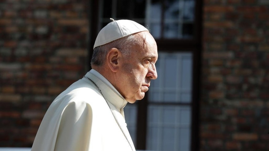 Pope Francis walks through the gate of the former Nazi German death camp of Auschwitz in Oswiecim, Poland, Friday, July 29, 2016.  Pope Francis paid a somber visit to the Nazi German death camp of Auschwitz-Birkenau Friday, becoming the third consecutive pontiff to make the pilgrimage to the place where Adolf Hitler's forces killed more than 1 million people, most of them Jews. (AP Photo/Gregorio Borgia)