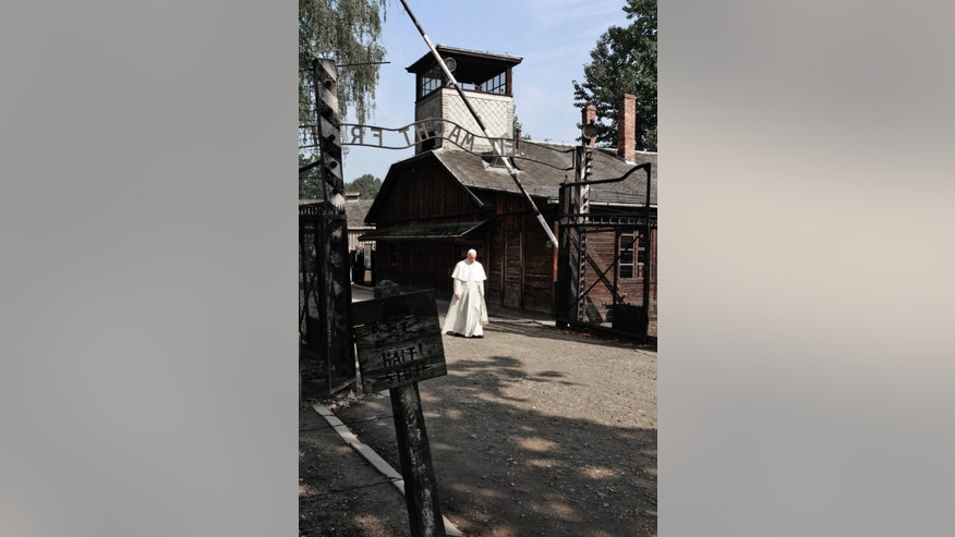 Pope Francis walks through the gate of the former Nazi German death camp of Auschwitz in Oswiecim, Poland, Friday, July 29, 2016. Pope Francis paid a somber visit to the Nazi German death camp of Auschwitz-Birkenau Friday, becoming the third consecutive pontiff to make the pilgrimage to the place where Adolf Hitler's forces killed more than 1 million people, most of them Jews. (AP Photo/Czarek Sokolowski)