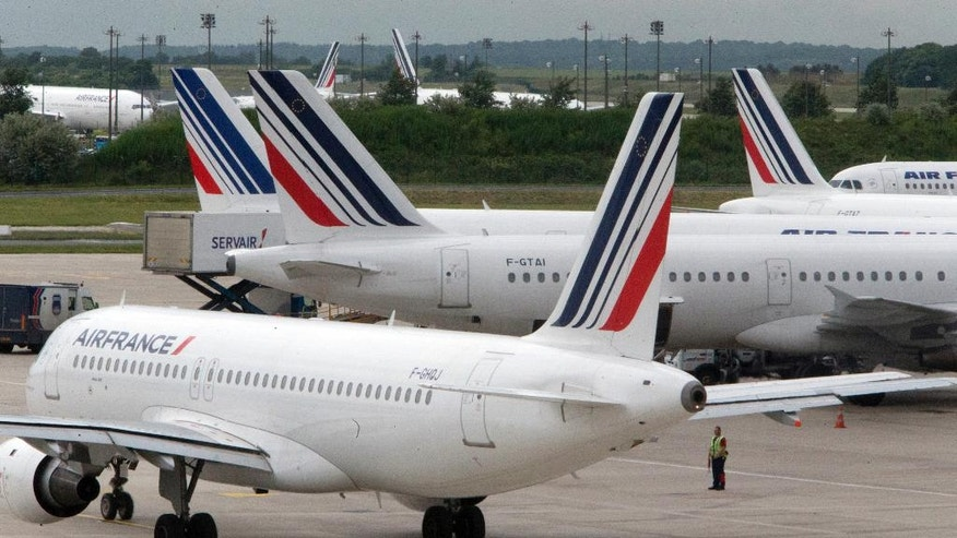 FILE -  This Thursday, June 13, 2013 file photo shows Air France planes parked on the tarmac at Roissy Charles de Gaulle airport near Paris, France, during an air traffic controllers strike. Air France has cancelled 10 percent of its long-distance flights Friday due to a strike by cabin crew amid mass departures for summer vacation. (AP Photo/Jacques Brinon, File)