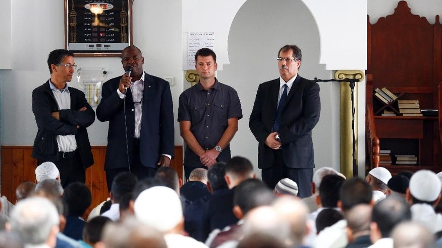 Saint-Etienne-du-Rouvray's Priest Auguste Moanda, second left, delivers his speech , flancked by Mohammed Karabila, President of the Muslim Regional Council of Normandy, left, Priest Pierre, center and Anouar Kbibech, President of the French Council of the Muslim Faith, right, as muslim worshippers attend the friday prayer at the Yahya Mosque, in Saint-Etienne-du-Rouvray, Normandy, France, Friday, July 29, 2016. Four days after the hostage taking in Saint-Etienne-du-Rouvray, officials and worshippers of the muslim community paid tribute to Priest Jacques Hamel and Christian community. (AP Photo/Francois Mori)