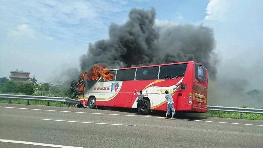 In this photo provided by Yan Cheng, a policeman and another man try to break the windows of a burning tour bus on the side of a highway in Taoyuan, Taiwan, Tuesday, July 19, 2016. Taiwanese investigators say the driver of the bus that crashed and burst into flames killing all 26 on board was driving drunk. Police coroners in Taoyuan county south of Taipei tested the driver's blood, urine and stomach contents and found all tested for alcohol concentrations above the legal limit. (Yan Cheng/Scoop Commune via AP)