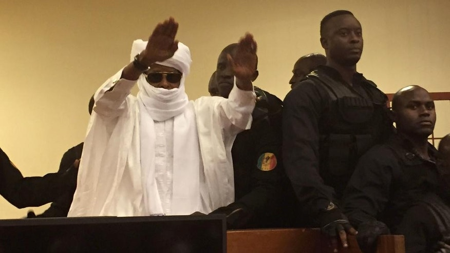 FILE-In this file photo taken on Monday, May 30, 2016, Chad's former dictator Hissene Habre raises his hands after sentencing during court proceedings in Dakar, Senegal. A tribunal ordered Chad's ex-dictator Hissene Habre on Friday, July 29, 2016, to pay more than 4,700 victims at least $17,000 each for abuses suffered during his time in power. (AP Photo/Carley Petesch,File)