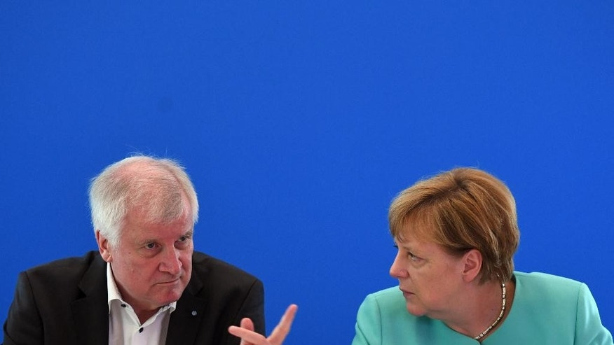 "GERMANY OUT - In this June 26, 2016 file picture Bavarian governor  Horst Seehofer left,  and German chancellor Angela Merkel attend a meeting in Potsdam, Germany. Bavaria's governor is distancing himself from Chancellor Angela Merkel's mantra that ""we will manage"" the refugee crisis following several attacks in Germany, including two committed by asylum-seekers and claimed by the Islamic State group. He said Saturday July 30, 2016 : ""With the best will, I can't embrace this sentence. The problems are too big for that and the solutions we have so far too unsatisfactory.""   (Ralf Hirschberger/dpa via AP,file)"
