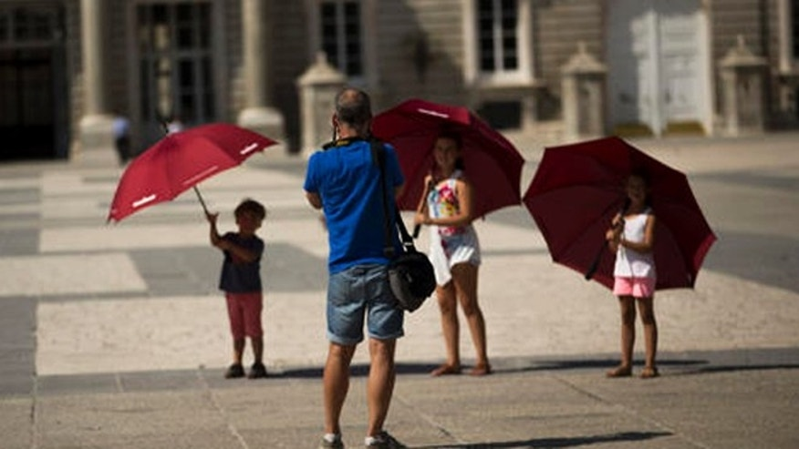EDS NOTE : SPANISH LAW REQUIRES THAT THE FACES OF MINORS ARE MASKED IN PUBLICATIONS WITHIN SPAIN.  Children pose for a photograph as they visit the Royal palace in Madrid, Spain, Friday, July 29, 2016. The number of tourists visiting Spain jumped by 12 percent in the first six months of 2016, as a mix of economic concerns and fears of extremist attacks is thought to have driven foreigners away from rival Mediterranean destinations. (AP Photo/Francisco Seco)