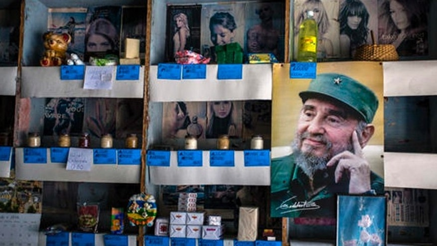 "In this July 23, 2016 photo, a picture of Cuban Revolution leader Fidel Castro is placed on the shelves of a state rationing store or ""bodega,"" ahead of his upcoming 90th birthday in Havana, Cuba. During 47 years in power, Fidel was a constant presence for Cubans but prohibited the statues, portraits and other tributes beloved by other total leaders. (AP Photo/Desmond Boylan)"