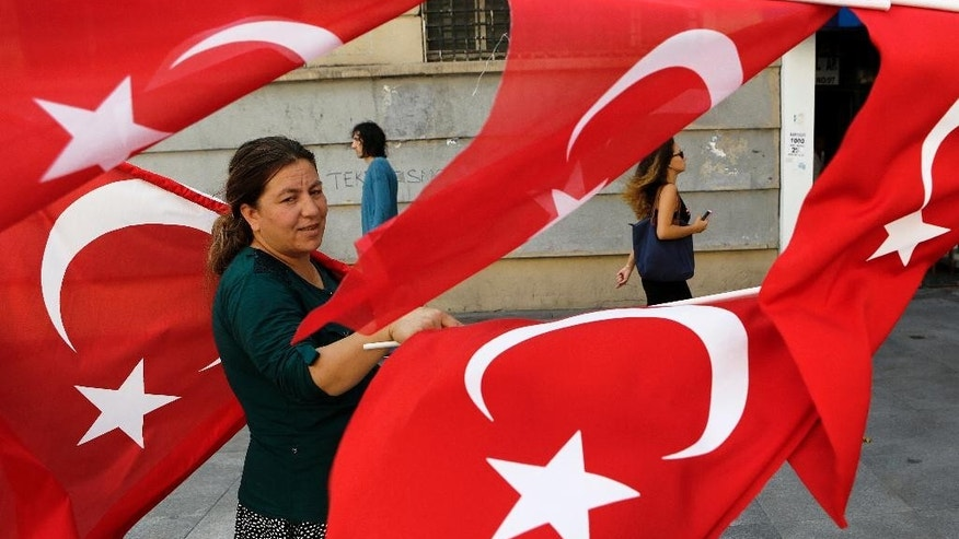 A woman sales Turkish flags in Istanbul, on Saturday, July 30, 2016. Turkey has demanded the United States extradite Fethullah Gulen, a cleric living in self-imposed exile in Pennsylvania whom it accuses of being behind the violent July 15 coup attempt that left more than 200 people dead. (AP Photo/Petros Karadjias)