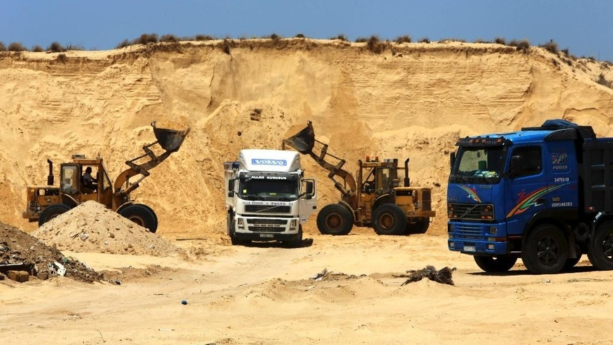 In this Wednesday, July 20, 2016 photo, Palestinian diggers  dump sand into a truck at the site of Al-Isra 2 housing project in Khan Younis, Gaza Strip. Hamas has begun handing out plots of public land to 40,000 civil servants loyal to the Islamic militant group, to make up for millions of dollars in salaries it owes them for the past two years.(AP Photo/Adel Hana)