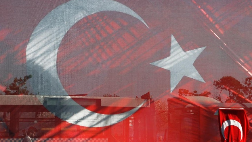 A man walks is seen left behind a giant Turkish flag at Besiktas area in Istanbul, on Friday, July 29, 2016.  The government crackdown in the coup's aftermath has strained Turkey's ties with key allies including the United States. (AP Photo/Petros Karadjias)