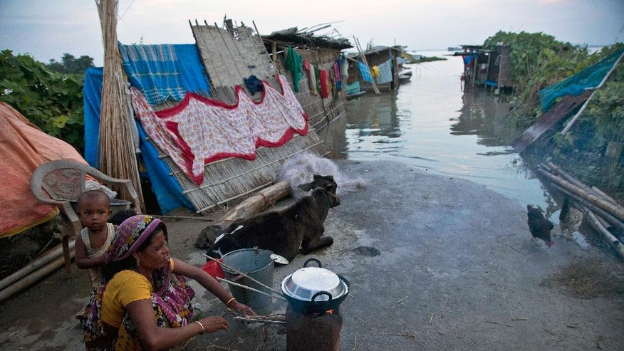 A woman prepares a meal by a flooded road at Sildubi village, in the northeastern Indian state of Assam, Friday, July 29, 2016. Torrential monsoon rains have caused widespread flooding in Assam state and forced around 1.2 million people to leave their water-logged homes. (AP Photo/Anupam Nath)