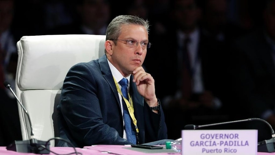 FILE - In this July 15, 2016 file photo, Puerto Rico Gov. Alejandro Garcia Padilla listens to U.S. Sen. Chuck Grassley speak during the National Governors Association meeting, in Des Moines, Iowa. Garcia Padilla signed a bill late Friday, July 29, 2016, letting the island's 78 municipal governments share administrative services as a cost-saving measure amid a deep fiscal crisis. (AP Photo/Charlie Neibergall, File)