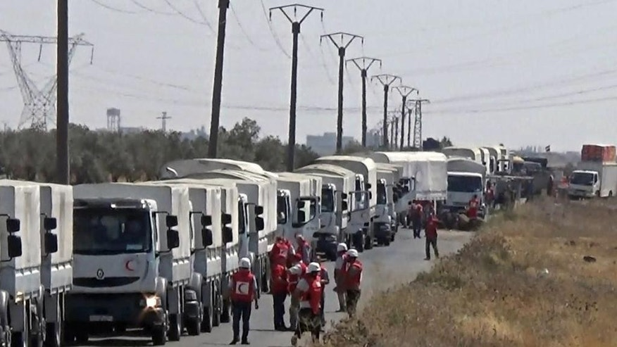 In this photo released by the Syrian official news agency SANA, a convoy of the Syrian Arab Red Crescent carries aid to southern besieged village of Nawa in the province of Daraa, Syria, Saturday, July 30, 2016. International aid organizations and the Syrian Arab Red Crescent have been distributing aid to besieged areas around Syria over the past weeks. (SANA via AP)