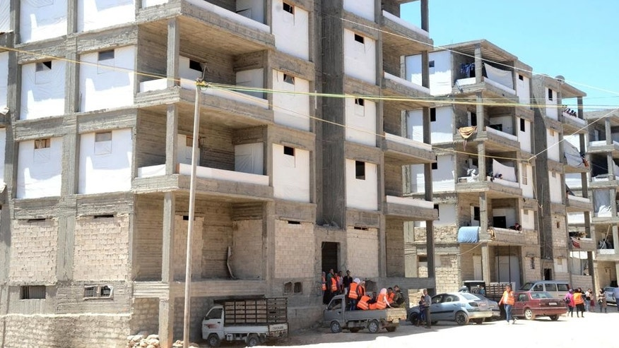 In this photo released on Friday, July 29, 2016 by the Syrian official news agency SANA, buildings prepared by the Syrian government to host people who will left rebel-held neighborhoods of the northern city of Aleppo, Syria. Syrian state media is reporting that dozens of families have started leaving besieged rebel-held neighborhoods in the northern city of Aleppo after the government opened safe corridors for civilians and fighters who want to leave. The Russian military says 169 civilians have left through the corridors since they were set up, but Syrian opposition activists say no civilians have left besieged parts of the city. (SANA via AP)