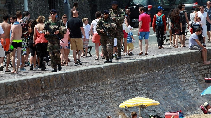 French soldiers patrols near the Biarritz's beach, southwestern France, Saturday, July 30, 2016. The challenge of protecting churches, synagogues, tourist haunts, beaches, summer festival sites, airports and train stations is among the most daunting tasks security forces have faced in recent times in France, and Europe. (AP Photo/ Bob Edme)
