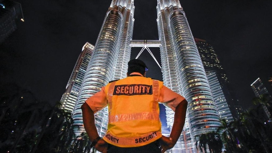 "FILE - In this Jan. 14, 2016 file photo, a security guard stands guard in front of Malaysia's iconic building, Petronas Twin Towers in Kuala Lumpur, Malaysia. Amnesty International has warned that a Malaysian security law that comes into force Monday, Aug. 1, 2016,  will give the government ""unchecked and abusive powers"" in a blow to human rights. (AP Photo/Joshua Paul, File)"