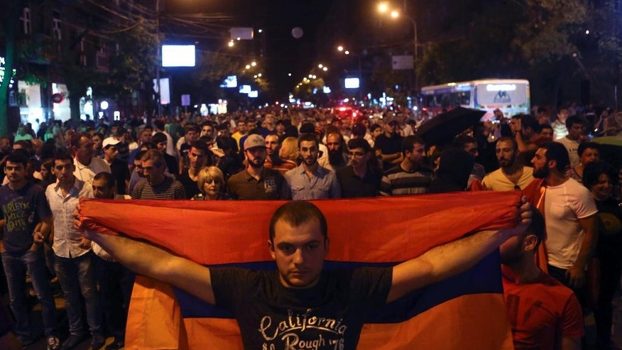Anti-government protesters, supporters of the armed group who have been holed inside a police station, prepare to march in Yerevan, Armenia, Saturday, July 30, 2016. Armed members of an opposition group barricaded inside a police station in Armenia's capital shot an officer dead on Saturday, police said. (Hrant Khachatryan/PAN Photo via AP)