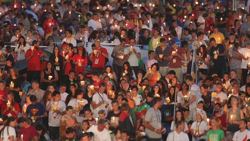 """Pilgrims participating in the World Youth Day 2016 hold candles at an evening vigil with Pope Francis at the Campus Misericordiae in Brzegi, near Krakow, Poland, Saturday, July 30, 2016. Francis challenged hundreds of thousands of young people who gathered in a sprawling Polish meadow to reject being a """"couch potato"""" who retreats into video games and computer screens and instead engage in social activism and politics to create a more just world. (AP Photo/Czarek Sokolowski)"""