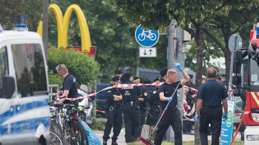 FILE - In this July 23, 2016 file picture police stand at a the crime scene  in Munich, Germany, where a shooting took place in front of a fast food restaurant leaving nine people dead the day before. A memorial service  for the nine victims of the shooting will be held Sunday July 31, 2016 in Munich.  German chancellor Angela Merkel and German President Joachim Gauck are expected to attend.  (AP Photo/Sebastian Widmann,file)