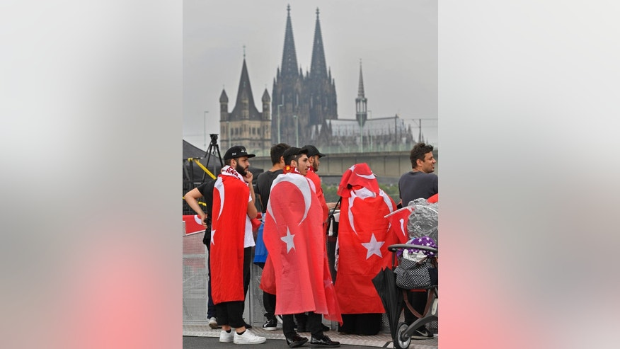 Turkish protesters wait for the start of a demonstration in front of the cathedral  in Cologne, Germany, Sunday, July 31, 2016. Supporters of Turkish President Recep Tayyip Erdogan are expected to demonstrate in Cologne amid heavy police presence. Some 30,000 participants are expected at Sunday's demonstration, which comes amid tensions following the failed coup attempt in Turkey and concern in Germany over the extent of the Turkish government's subsequent crackdown. (AP Photo/Martin Meissner)