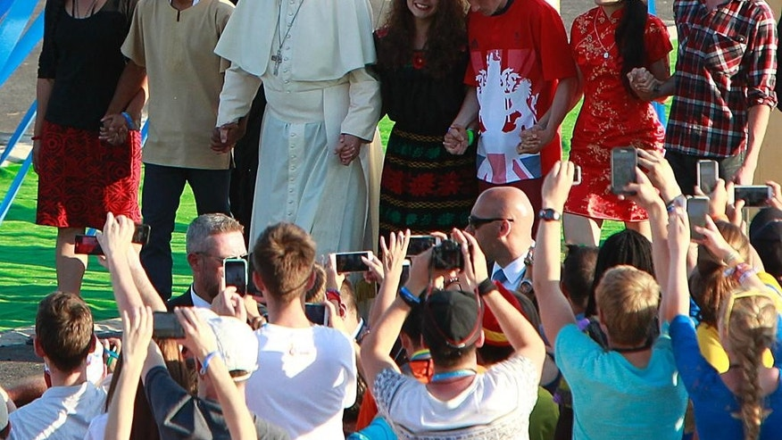 Pope Francis, accompanied by youths, passes through the Door of Mercy ahead of a prayer vigil on the occasion of the World Youth Days, in Campus Misericordiae in Brzegi, near Krakow, Poland, Saturday, July 30, 2016. The 79-year-old Francis has had an unrelenting schedule since he arrived in Poland on Wednesday for World Youth Days, a global Catholic gathering which culminates Sunday. (AP Photo/Czarek Sokolowski)