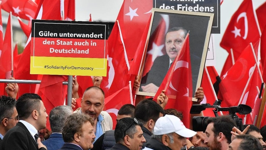 Turkish protestors hold a banner reading 'Gulen infiltrers the state also in Germany' during a demonstration  in Cologne, Germany, Sunday, July 31, 2016.  Supporters of Turkish President Recep Tayyip Erdogan demonstrate in Cologne amid heavy police presence. Some 30,000 participants are expected at Sunday's demonstration, which comes amid tensions following the failed coup attempt in Turkey and concern in Germany over the extent of the Turkish government's subsequent crackdown.(AP Photo/Martin Meissner)