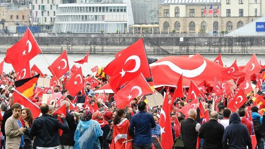 Turks hold national  flags during a demonstration in Cologne, Germany, Sunday, July 31, 2016.   Supporters of Turkish President Recep Tayyip Erdogan demonstrate in Cologne amid heavy police presence. Some 30,000 participants are expected at Sunday's demonstration, which comes amid tensions following the failed coup attempt in Turkey and concern in Germany over the extent of the Turkish government's subsequent crackdown. (AP Photo/Martin Meissner)