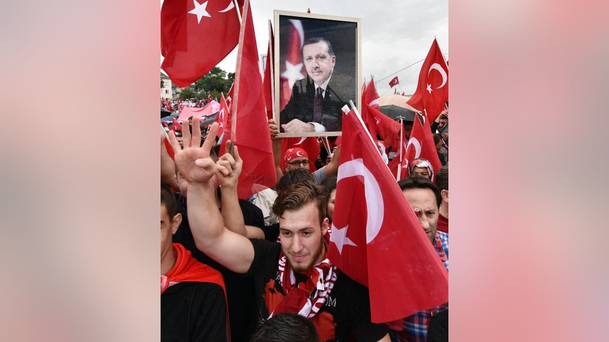 A Turkish protestor holds a portrait of president Erdogan during a demonstration in Cologne, Germany, Sunday, July 31, 2016.  Supporters of Turkish President Recep Tayyip Erdogan demonstrate in Cologne amid heavy police presence. Some 30,000 participants are expected at Sunday's demonstration, which comes amid tensions following the failed coup attempt in Turkey and concern in Germany over the extent of the Turkish government's subsequent crackdown. (AP Photo/Martin Meissner)