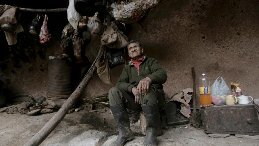 In this July 28, 2016 photo, Pedro Luca poses for a picture inside a mountain cavern near San Pedro de Colalao, Argentina's northern province of Tucuman. Luca has traveled back to prehistoric times to find harmony with nature and his self: disillusioned with civilization and city life, the 79-year old man has lived for the past 40 years in the cavern, known for its Inca ruins and outstanding Andean landscape. (AP Photo/Alvaro Medina)