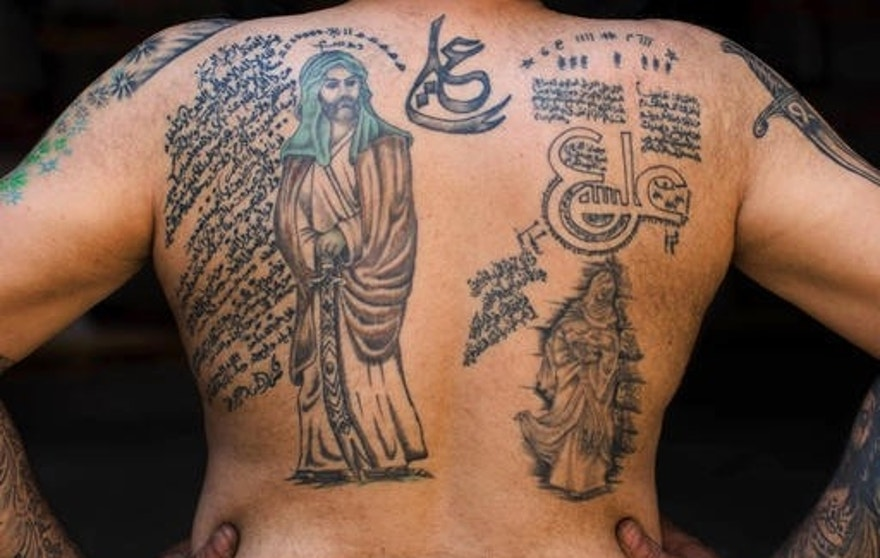 In this Tuesday, May 10, 2016 photo, Ali Hussein Nasreddine, 50, poses for a photo showing off his tattoos of Shiite Muslim religious slogans and Shiite Muslims' first Imam Ali, in the southern suburb of Beirut, Lebanon. A growing number of Shiite Muslims in Lebanon are getting tattoos with religious and other Shiite symbols since the civil war in neighboring Syria broke out five years ago, fanning sectarian flames across the region. (AP Photo/Hassan Ammar)