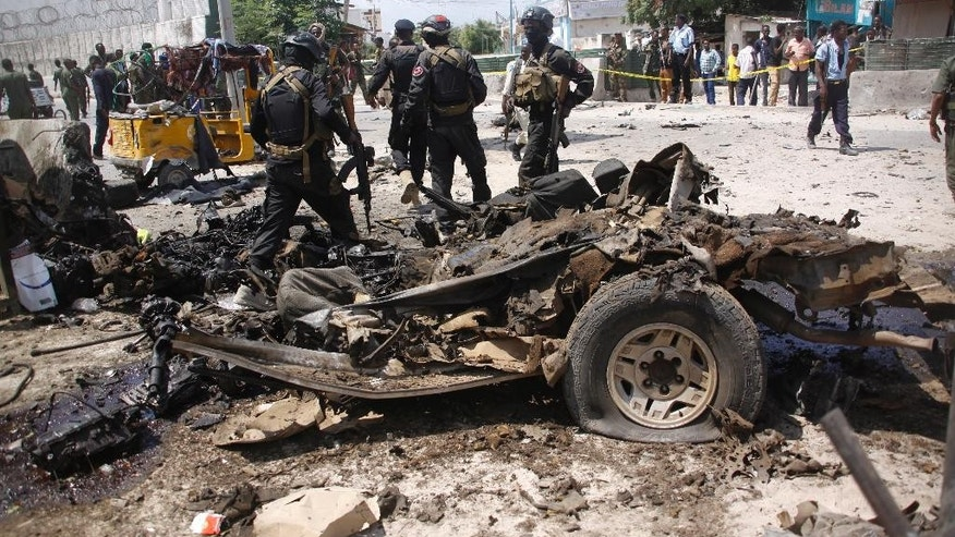 Somali soldiers stand near the wreckage of a car used in a suicide car bomb attack outside the Criminal Investigation Department (CID) in Mogadishu, Somalia, Sunday, July 31, 2016. Two suicide bombers detonated an explosives-laden car outside the Criminal Investigation Department (CID) in Mogadishu, killing 9 people, including two bombers, and others were injured, a Somali police official said. (AP Photo/Farah Abdi Warsameh)