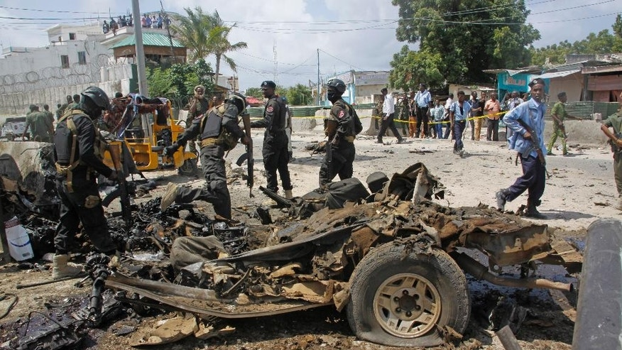 Somali soldiers stand near the wreckage of a car used in a suicide car bomb attack outside the Criminal Investigation Department (CID) in Mogadishu, Somalia, Sunday, July 31, 2016. Two suicide bombers detonated an explosives-laden car outside the Criminal Investigation Department (CID) in Mogadishu, killing 9 people, including two bombers, and others were injured a Somali police official said. (AP Photo/Farah Abdi Warsameh)