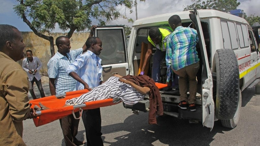 Somalis carry a wounded to an ambulance, who was injured in a suicide car bomb attack outside The Criminal Investigation Department (CID) in Mogadishu, Somalia, Sunday, July 31, 2016. Two suicide bombers detonated an explosives-laden car outside the Criminal Investigation Department (CID) in Mogadishu, killing 9 people, including two bombers, and others were injured, a Somali police official said. (AP Photo/Farah Abdi Warsameh)