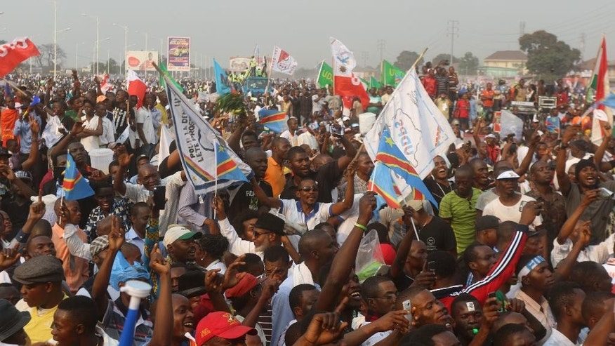 """Supportes of Congo opposition leader Etienne Tshisekedi during a political rally in Kinshasa, Congo, Wednesday, July 31, 2016. Several thousand people, many wearing the blue, yellow and red colors of Congo's flag, gathered near the Stadium of Martyrs in Kinshasa Sunday holding banners that said """"No to a third term."""" (AP Photo/John Bompengo)"""