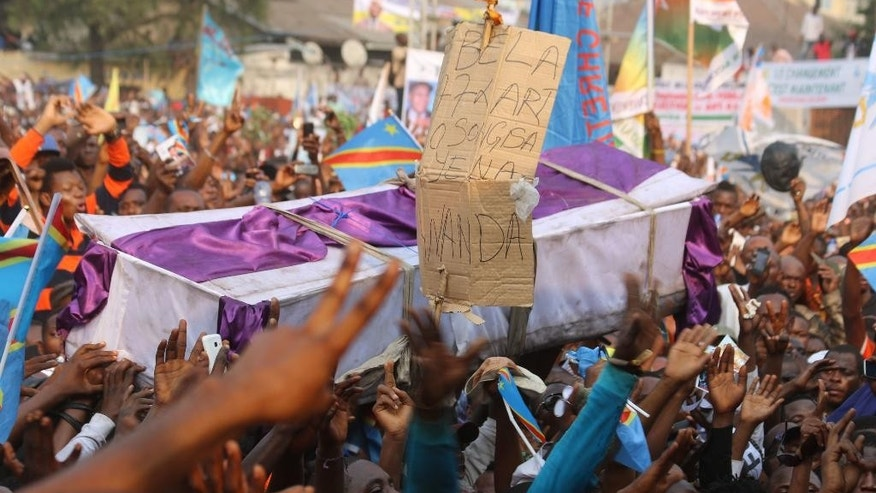 """Supportes of Congo opposition leader Etienne Tshisekedi carry a symbolic casket during a protest against a third term for Congo President Joseph Kabila, during a political rally in Kinshasa, Congo, Wednesday, July 31, 2016. Several thousand people, many wearing the blue, yellow and red colors of Congo's flag, gathered near the Stadium of Martyrs in Kinshasa Sunday holding banners that said """"No to a third term."""" (AP Photo/John Bompengo)"""