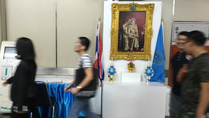 Commuters walk past a portrait of Thailand's Queen Sirikit, consort of King Bhumibol Adulyajej, at a BTS station in central Bangkok, Sunday, July 31, 2016. The 83-year-old recently suffered a lung infection and was moved on July 24 from Bangkok's Siriraj Hospital, where the king has been living for most of the past few years, to Chulalongkorn Hospital for treatment of a minor lung inflammation and blood infection. (AP Photo/Grant Peck)