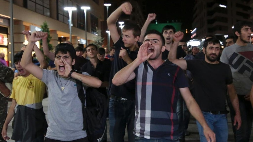 Protesters shout anti-government slogans during a night rally to support the radical opposition group gunmen in the Republican Square in Yerevan, Armenia, Sunday, Aug. 31, 2016.  All 20 gunmen inside a police compound in Armenia's capital surrendered Sunday, ending a two-week standoff that left two police officers dead and several wounded on both sides, the security service said.   (Aram Kirakosyan, PAN Photo via AP)