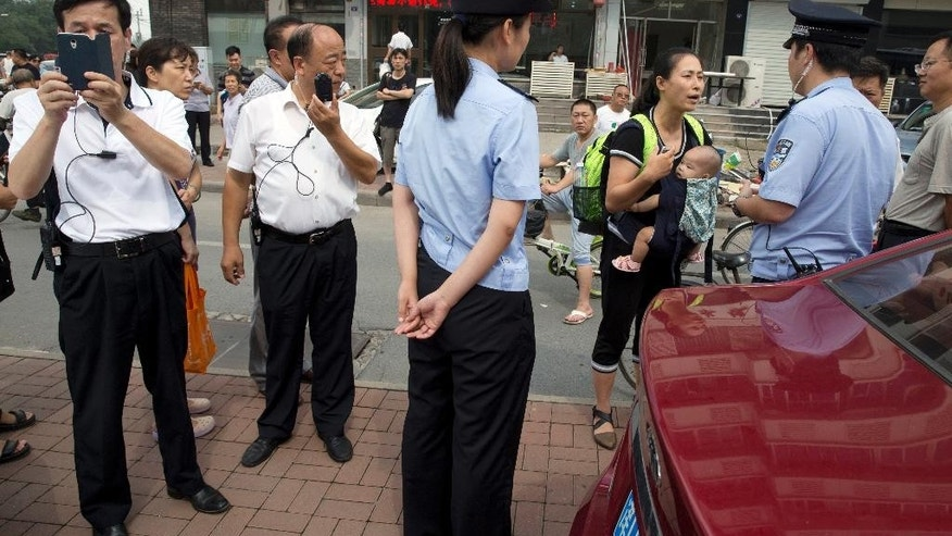 Yuan Shanshan, third right, the wife of detained Chinese lawyer Xie Yanyi, carries her child as she talks to a police officer while other plain clothes security personnel film journalists near the Tianjin No. 2 Intermediate People's Court in northern China's Tianjin Municipality on Tuesday, Aug. 2, 2016. The court in the northern Chinese city of Tianjin has begun to try the first of four human rights advocates charged with subversion of state power, marking the first publicly acknowledged hearing in a yearlong case shrouded in secrecy and involving hundreds of Chinese human rights activists.(AP Photo/Ng Han Guan)