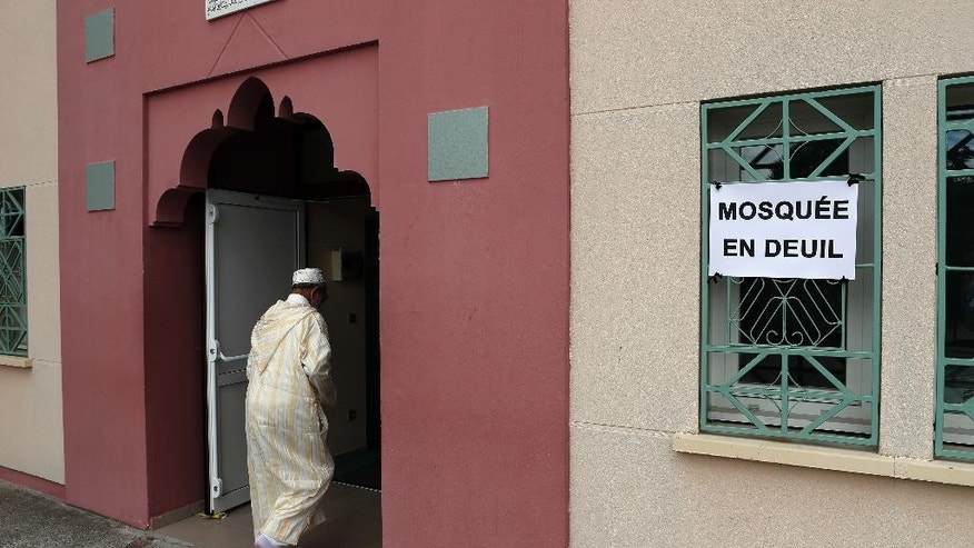 "FILE - In this July 29, 2016 file photo, a Muslim worshipper walks past a poster reading ""Mourning Mosque"" for the friday prayer at the Yahya Mosque, in Saint-Etienne-du-Rouvray, Normandy, four days after the hostage taking in Saint-Etienne-du-Rouvray. The head of the French Muslim Council says a new foundation will be created to help finance the construction and running of mosques in the country and keep out radical benefactors. (AP Photo/Francois Mori, File)"